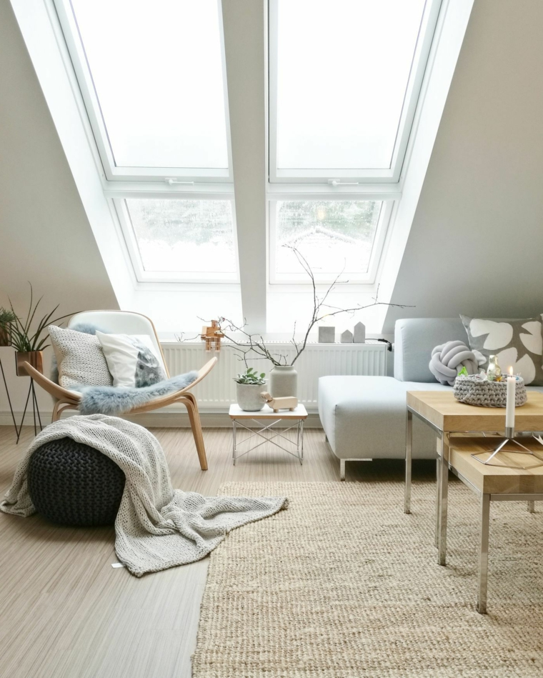 Soggiorno con divano grigio, sottotetto con grande finestra, mansarda con pavimenti in legno