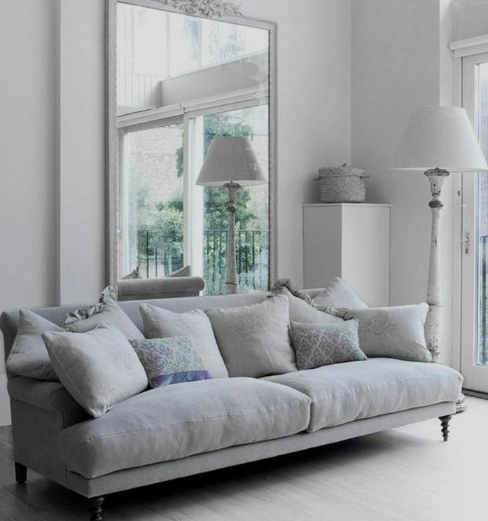 Soggiorno bianco e grigio, divano con cuscini colorati, grande specchio da parete