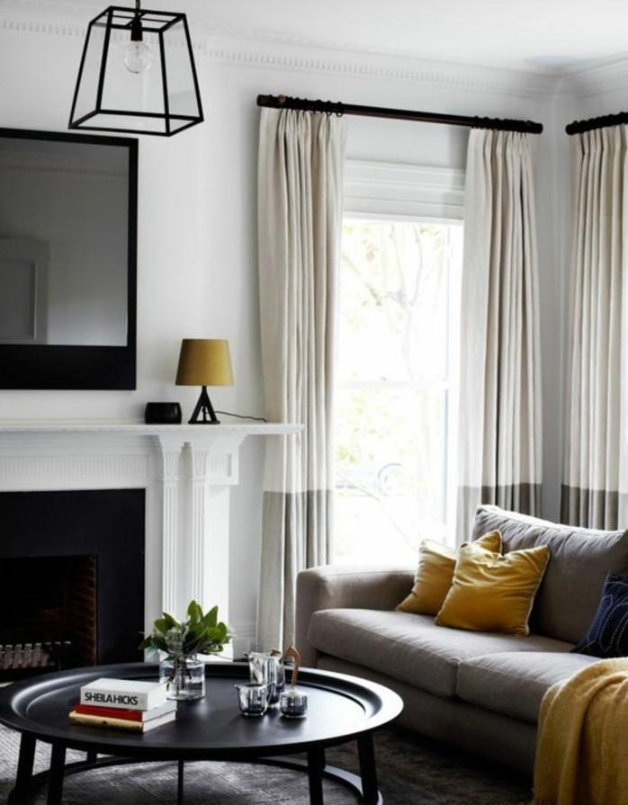 Soggiorno bianco e grigio, divano con cuscini gialli, tavolino basso rotondo
