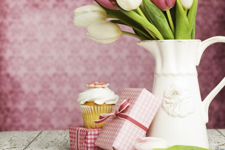 Vaso con fiori freschi, pacchetto regalo con nastro, cupcake con panna montata