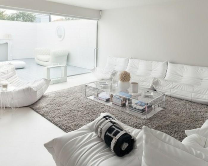 Mobili da soggiorno di colore bianco, divano in tessuto, tavolino basso di vetro