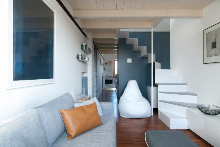 Sottetetto con soffitto di legno, divano di colore grigio, salotto stretto e lungo