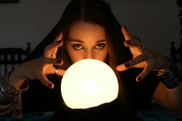 Ragazza con trucco da strega, sfera rotonda luminosa, costume semplice Halloween