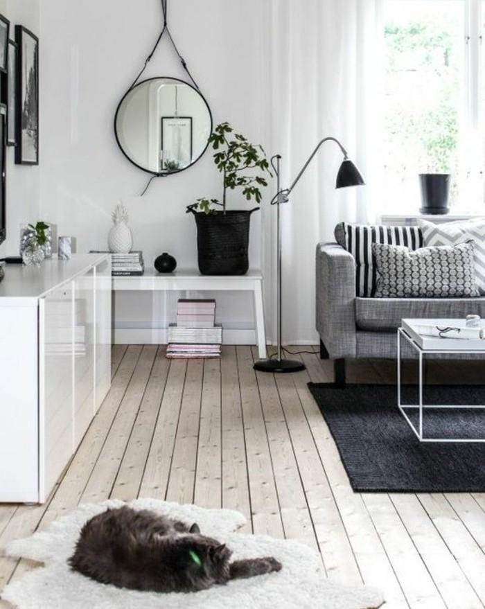 Pavimento di legno, salotto con divano, tavolino bassi di metallo bianco