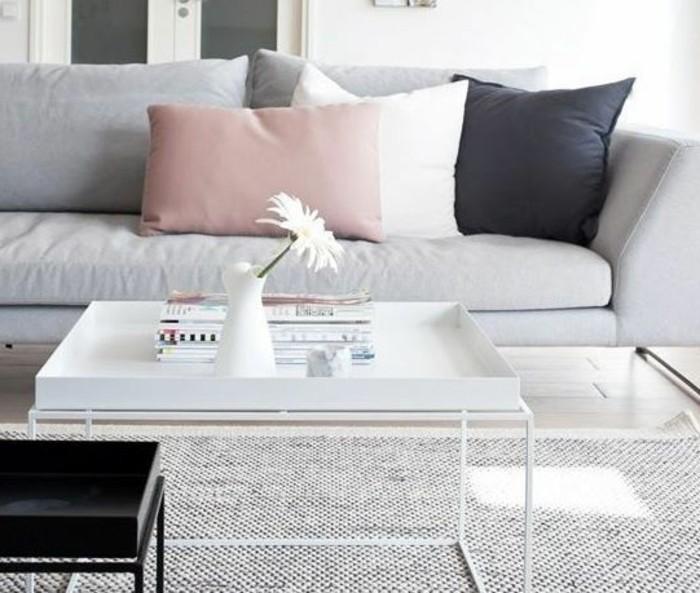 Tavolino basso di colore bianco, divano con cuscini colorati, salotto con tappeto grigio