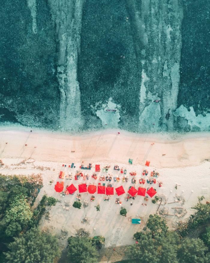 La spiaggi di un mare, ombrelloni di colore rosso, foto per schermo telefono