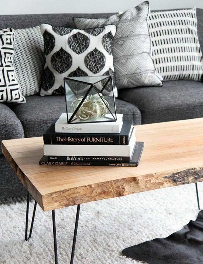 Soggiorno con tavolino di legno, divano di colore grigio, decorazione con libri