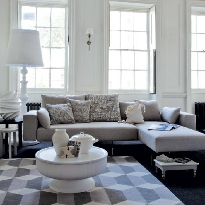 Soggiorno con divano di colore grigio, tavolino di legno bianco, tappeto con disegni geometrici