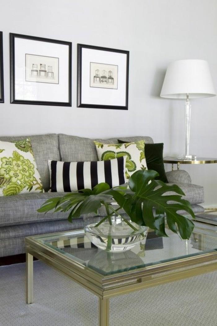 Tavolino basso di vetro, divano di colore grigio, parete bianca con fotografie