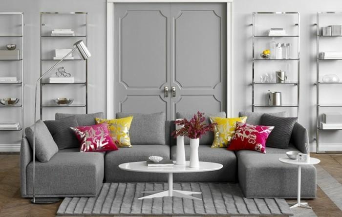 Salotto con porta di legno, divano con due isole, tavolino bianco forma ovale