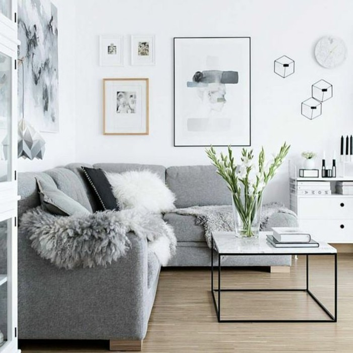 Salotto con divano grigio, soggiorno con pareti bianche, tavolino basso di colore bianco lucido