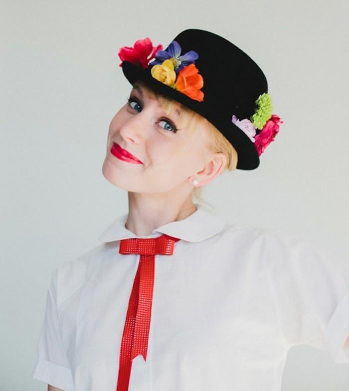 Ragazza con capelli biondi, cappello nero decorato con fiori