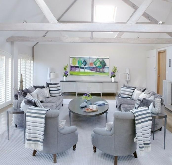 Salotto con divani, soffitto con travi in legno, pareti di colore bianco, pavimento con tappeto
