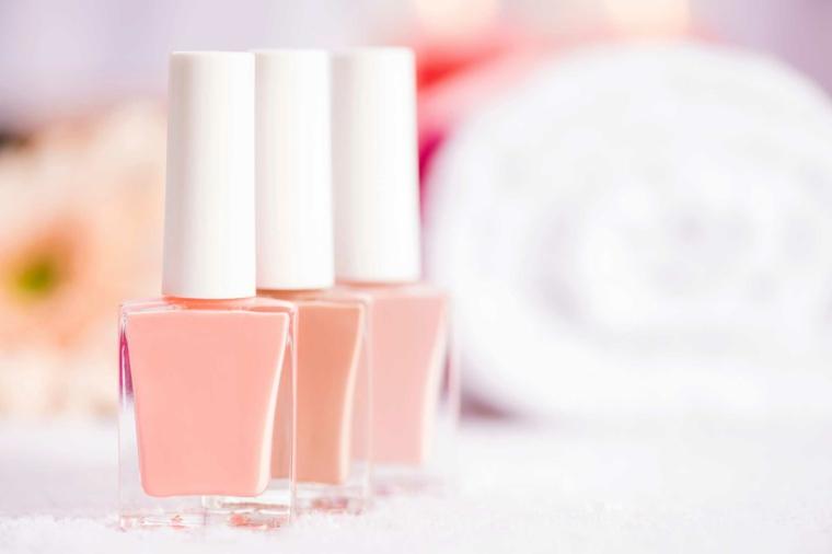 Tre bottiglie di smalto, smalto colore rosa, tappi di plastica