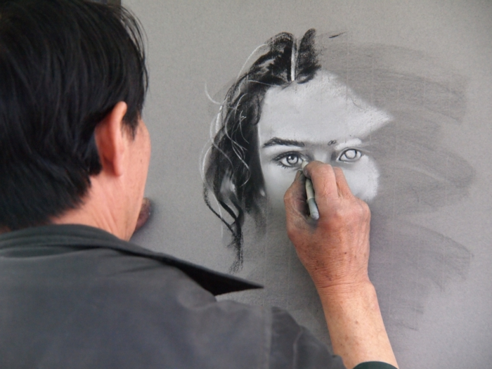 Un uomo che disegna con i pastelli, disegno viso donna