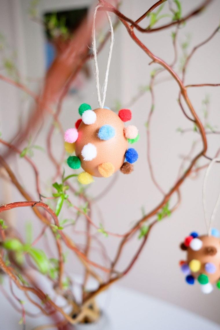 Uova di Pasqua fai da te, uovo con pom pom, rametti di albero pasquale