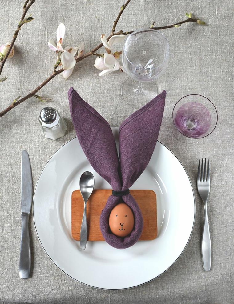Segnaposto con uovo, tovagliolo piegato, decorazioni pasquali