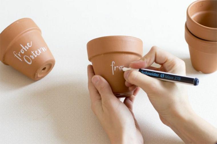 Lavoretti per Pasqua fai da te, vaso di terracotta, scritta con pennarello bianco