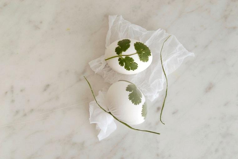 Uova di Pasqua fai da te, uovo con foglie di prezzemolo, calza bianca trasparente