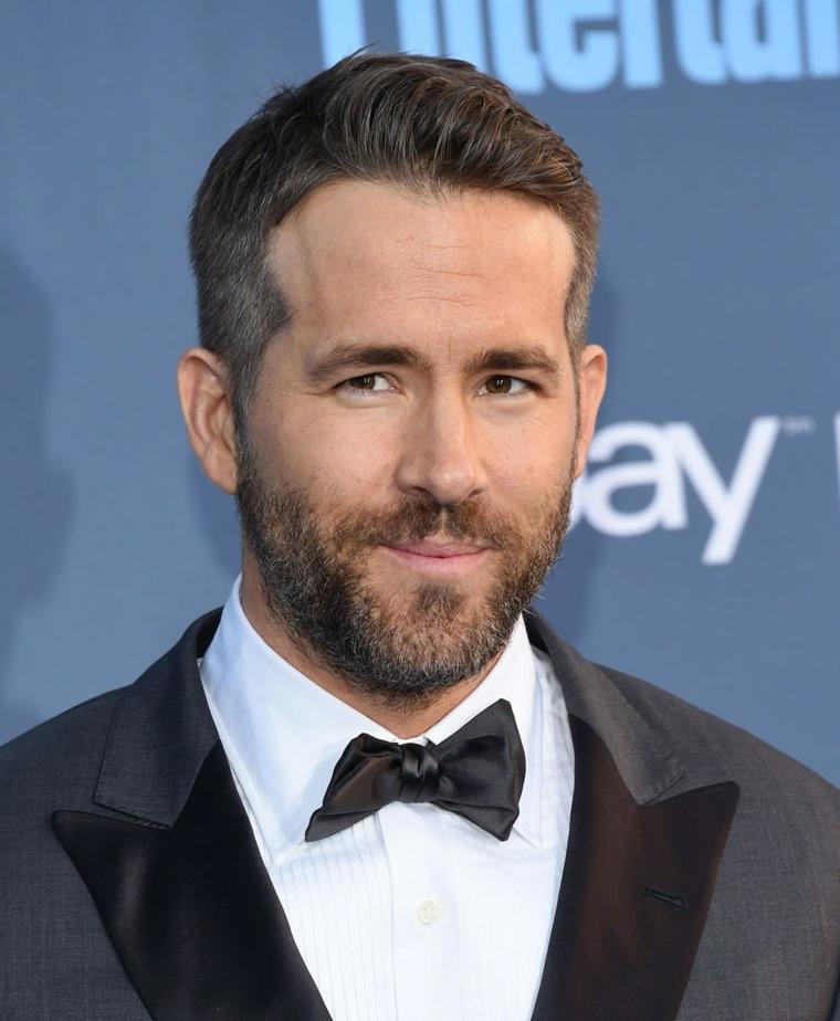 L'attore Ryan Reynolds, capelli rasati ai lati, colore capelli castano chiaro