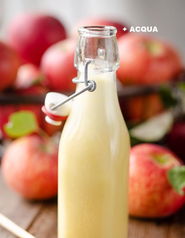 Vinaigrette aceto di mele, bottiglia di vetro, tavolo con mele