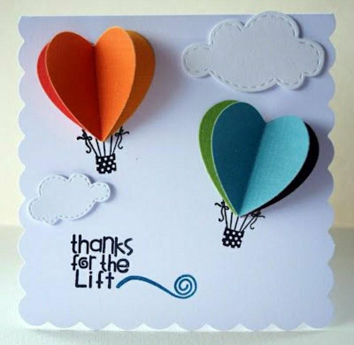 Cartolina con mongolfiere, scritta con auguri, foglio bianco con disegni