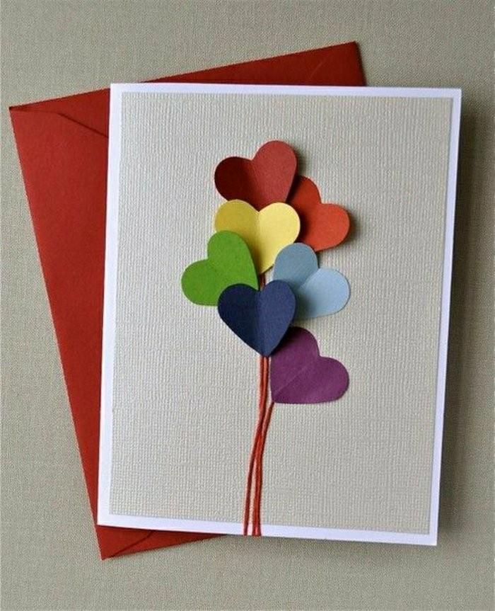 Busta di colore rosso, cartolina con cuori, bigliettino fatto a mano