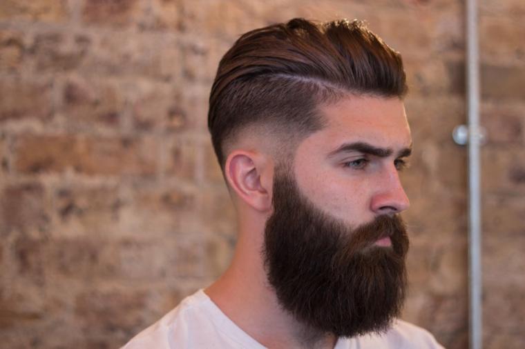 Uomo con barba lunga, taglio di capelli rasato, acconciature stile pompadour