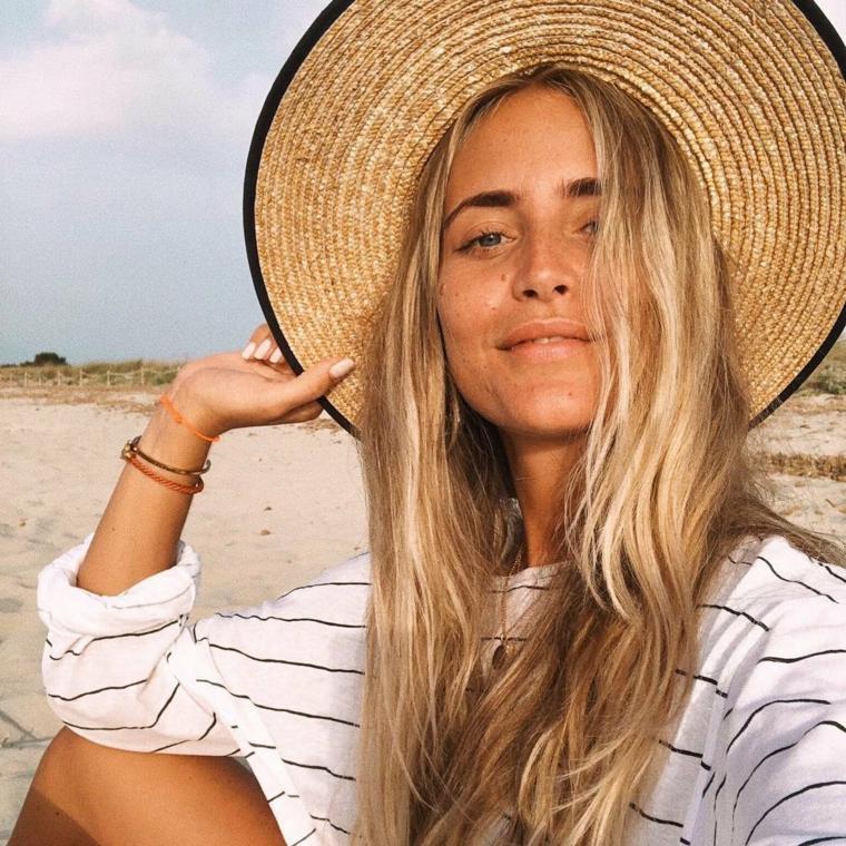 Schiarire i capelli, ragazza con capelli biondi, cappello di paglia, spiaggia con sabbia