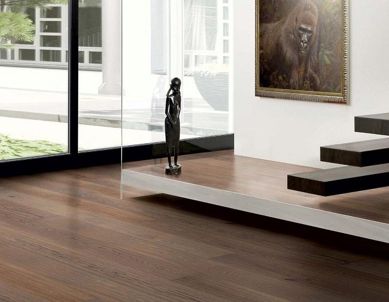 Casa con scale, pavimento in legno, lastre di colore scuro, parete di vetro