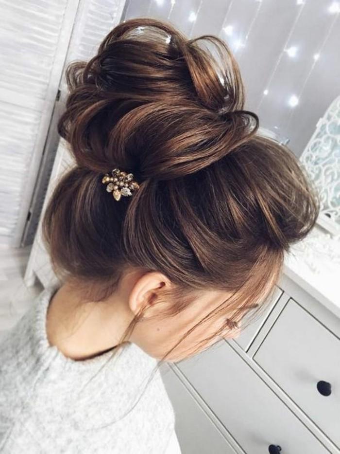 Capelli legati a chignon, capelli di colore castano, fermagli in metallo