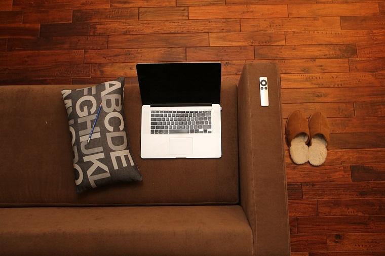 Soggiorno con divano marrone, pavimento in legno, decorazione con cuscino