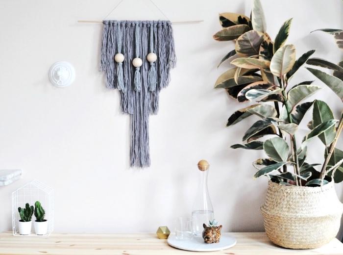 Parete di colore bianco, vaso con piante, bastone di legno con fili annodati