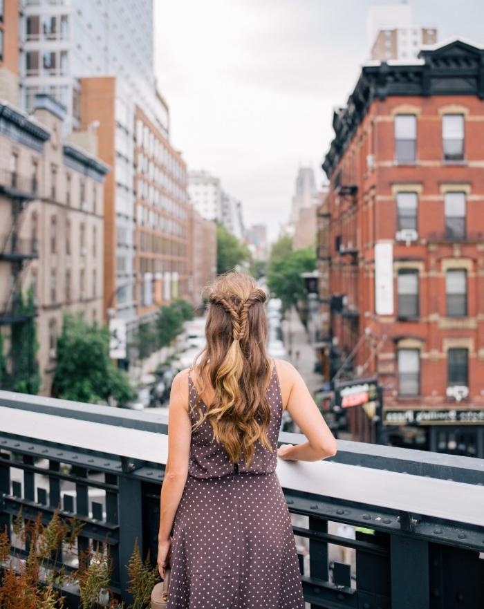 Donna su un ponte, palazzi di una città, acconciature belle, capelli di colore biondo