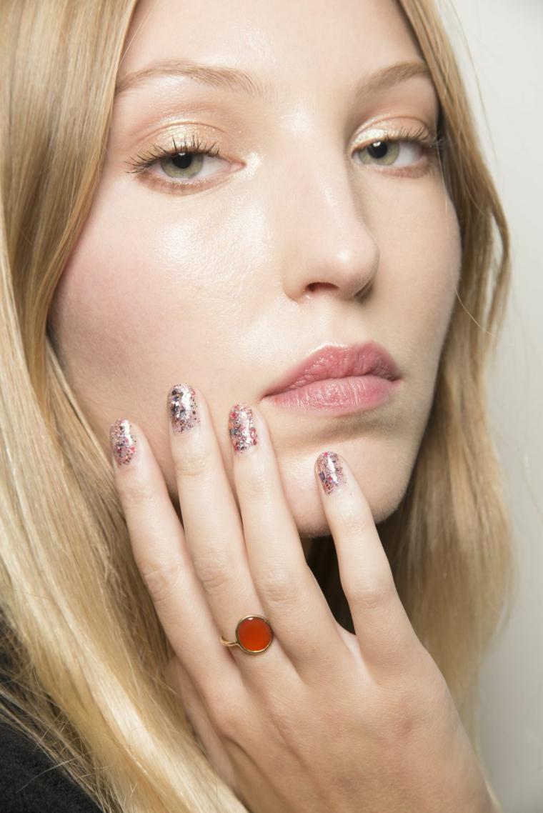 Manicure unghie corte, smalto con glitter, donna con capelli biondi