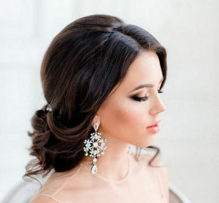 Capelli di colore nero, pettinatura a chignon, orecchini pendenti