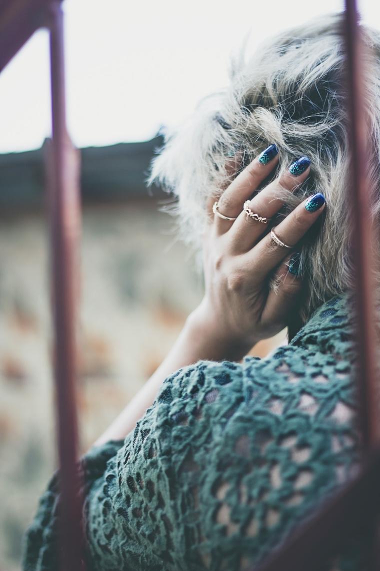 Unghie bellissime, mano con anelli, smalto blu e verde