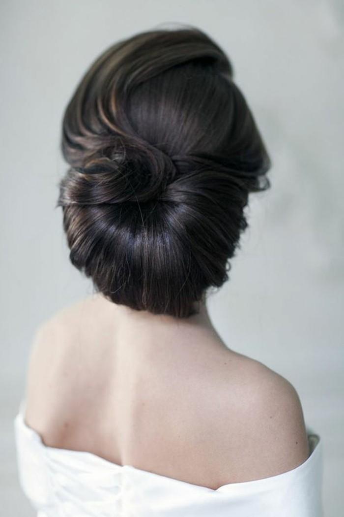 Capelli legati a chignon, capelli di colore nero, abito da sposa bianco