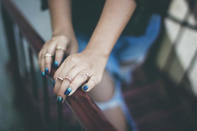 Disegni sulle unghie, smalto blu con disegni, anelli sulle dita