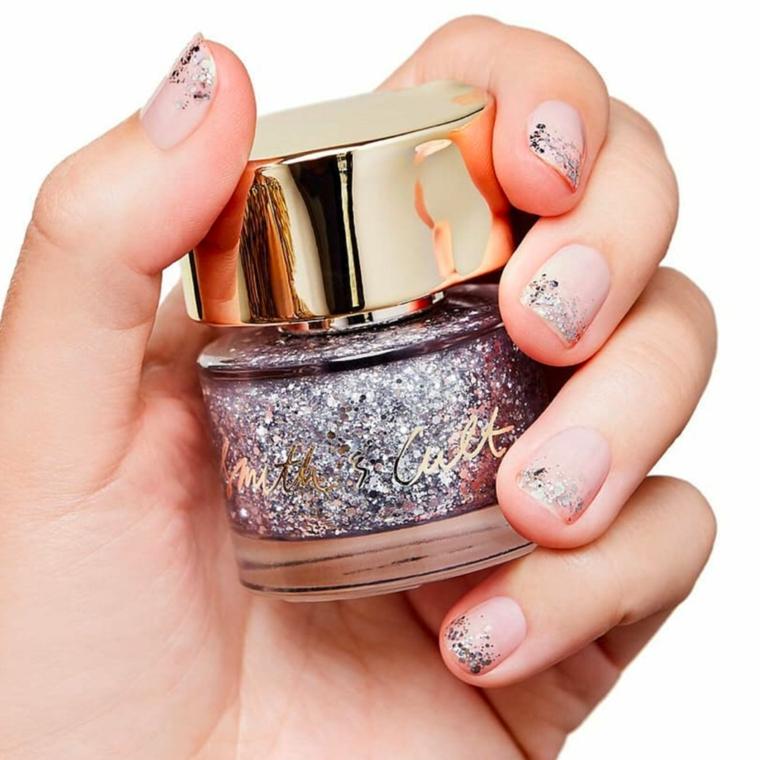 Manicure unghie corte, bottiglietta con smalto glitter, mano di una donna