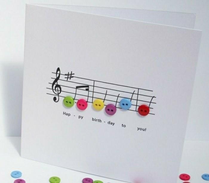 Foglio bianco piegato, disegno note musicali, decorazioni con bottoni