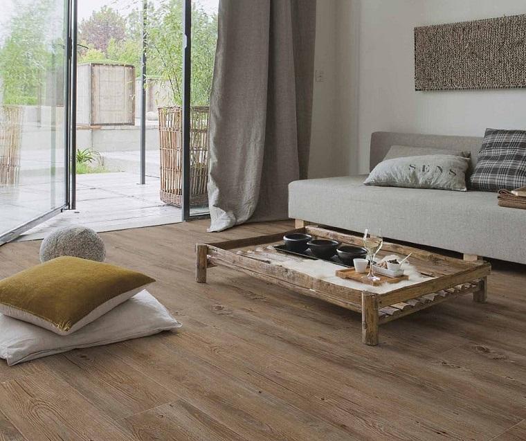 Soggiorno con divano, tavolino di legno, pavimento in vinile, tende di colore grigio