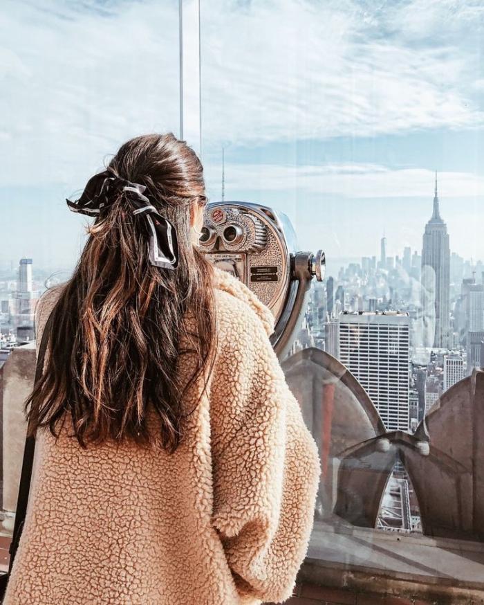Ragazza guarda dal binocolo, capelli castani legati, foulard per capelli