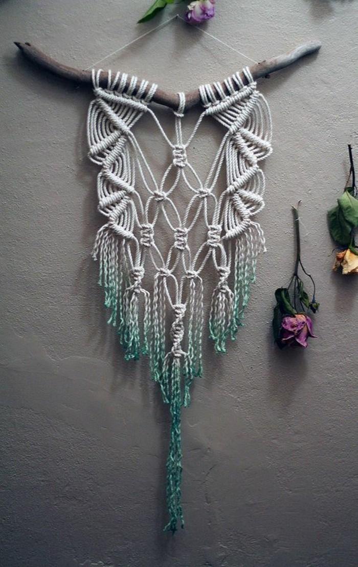 Macrame con fili, bastone di legno, decorazioni per un muro