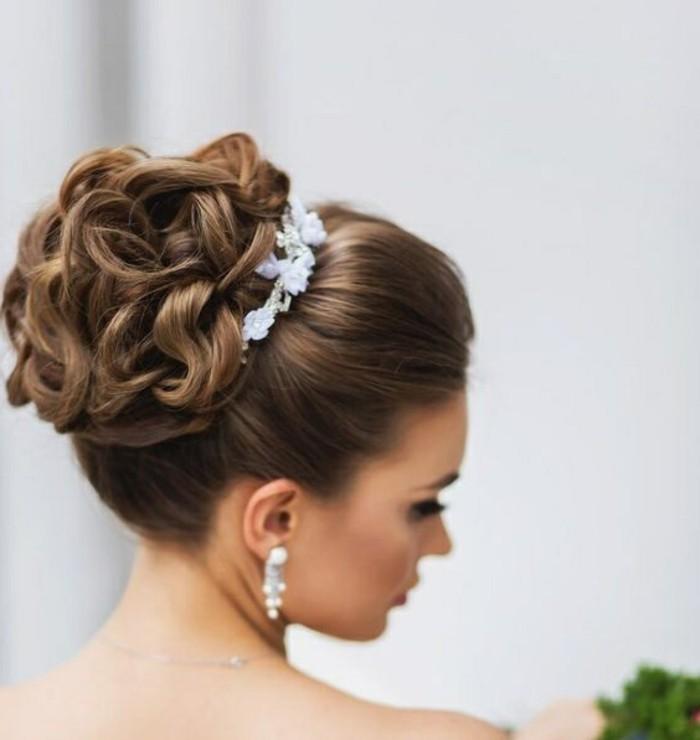 Chignon con capelli ricci, diadema con fiori, orecchini da sposa pendenti