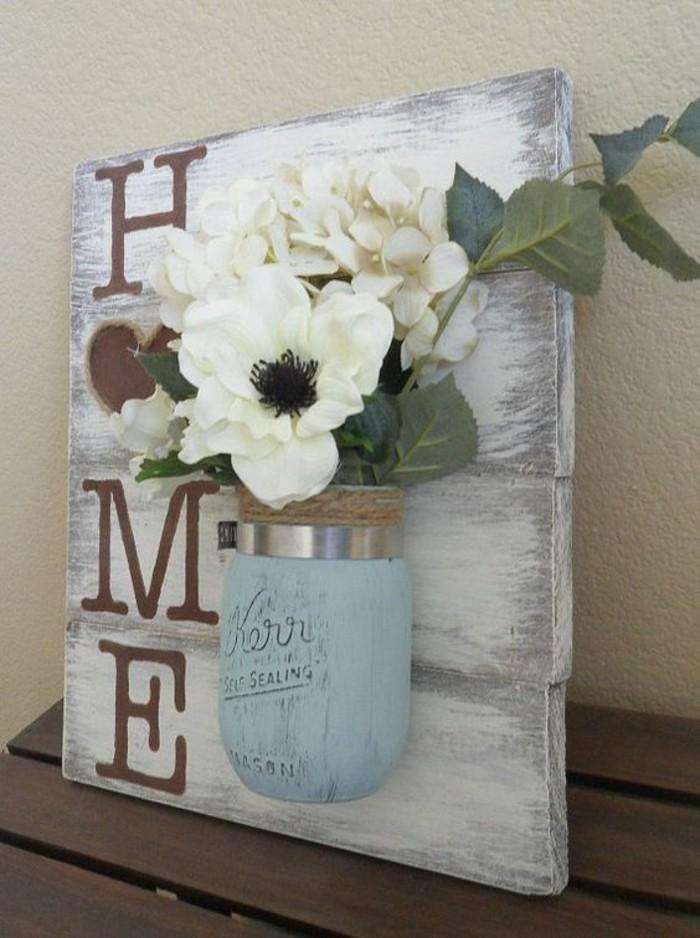 Legno con scritta home, barattolo di vetro con fiori