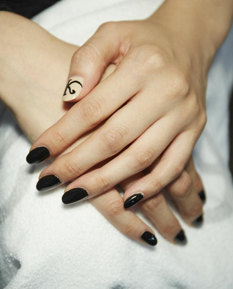 Manicure unghie corte, smalto di colore nero, accent nail colore beige, disegno lettera K