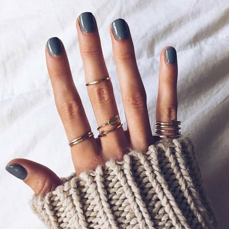 Anelli sulle dita, smalto di colore grigio, maglione di lana