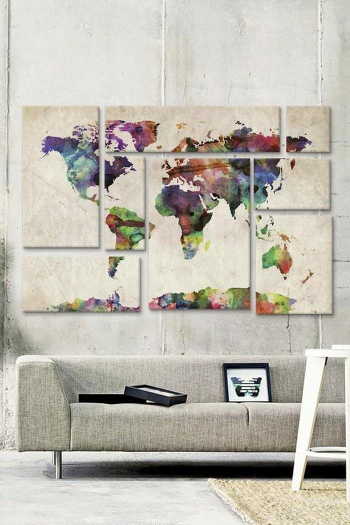 Salotto con divano grigio, parete con quadri, quadro spezzato di un mappamondo
