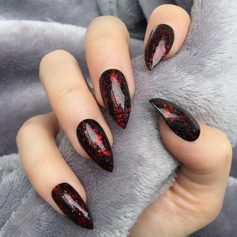 Stiletto con smalto nero, smlto nero effetto marmo rosso, mano di una donna